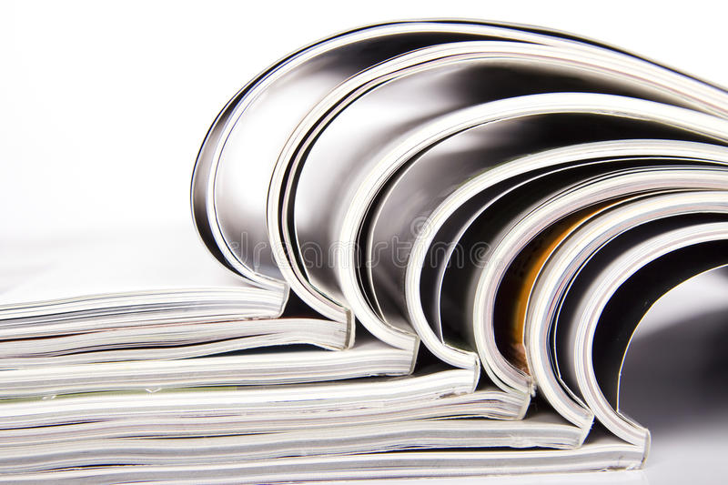 Magazines. A stack of magazines sitting on a table stock image