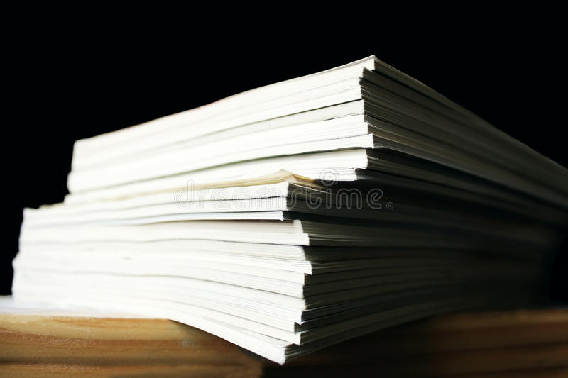 Magazines. Photo of many magazines stacked on one another on the table, in the black background stock photography