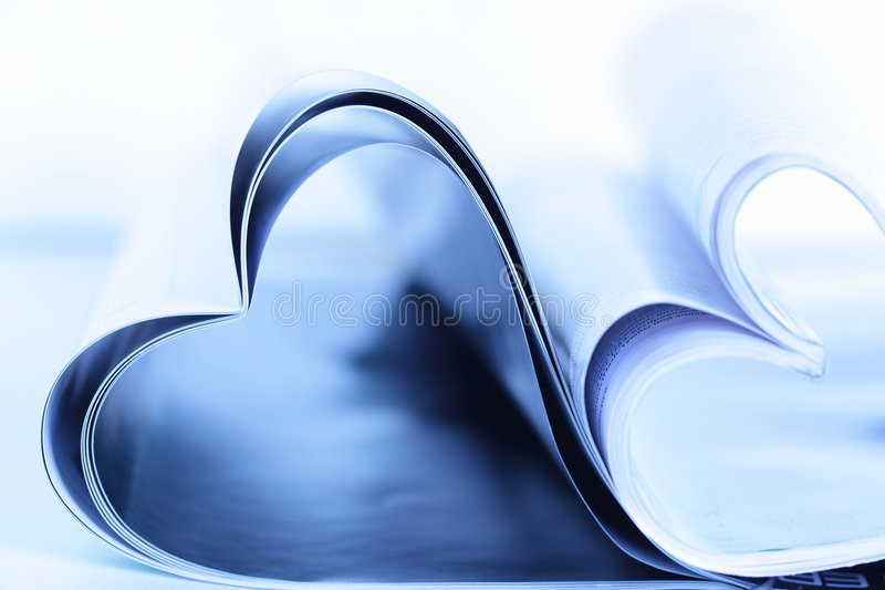 Magazines. Two magazines folded to heart shape on table royalty free stock photo