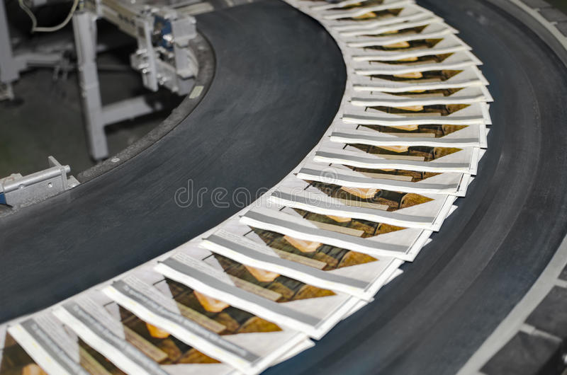 Magazines on conveyor belt in print plant. Working print machine with magazines on conveyor belt stock images