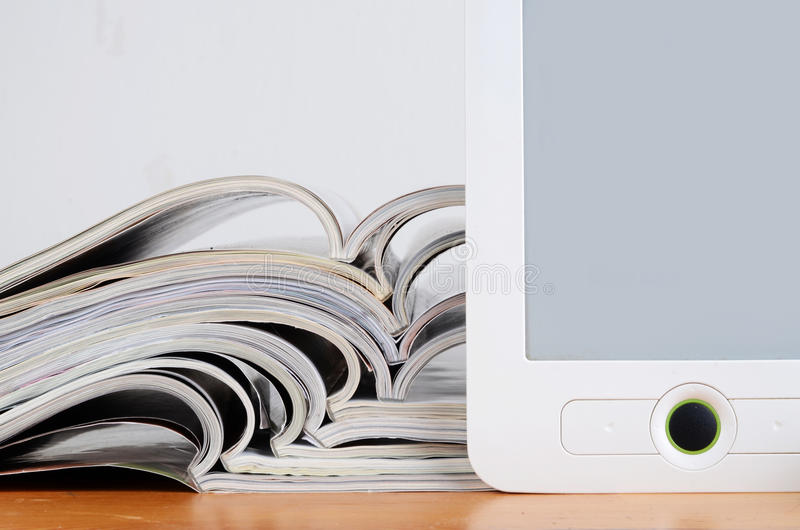 Magazines and ereader. Stack of magazines and ereader royalty free stock image