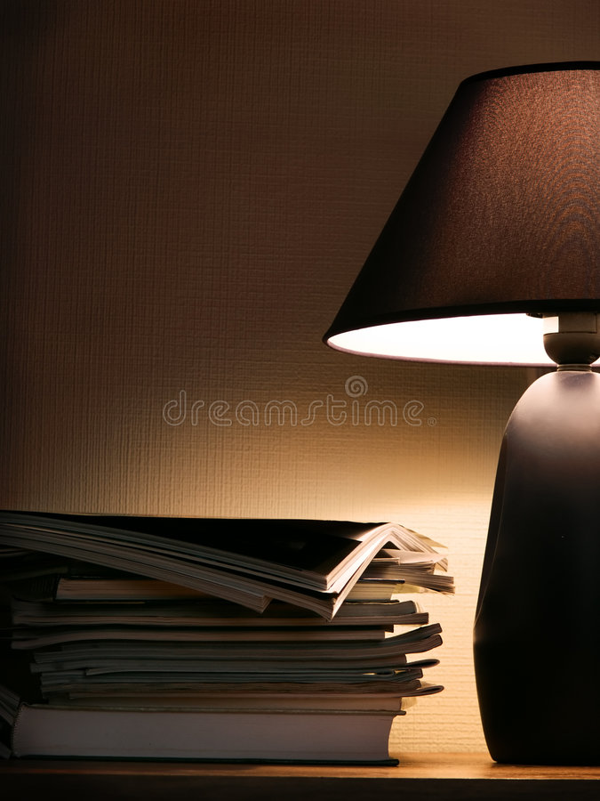 Magazines under evening lamp light royalty free stock images
