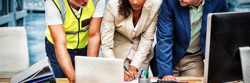 Magazynowi kierownicy i pracownik dyskutuje z laptopem obrazy royalty free