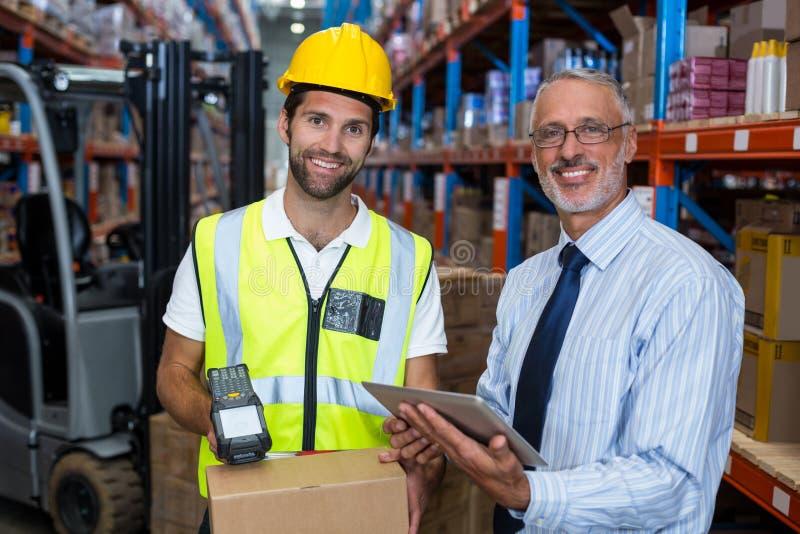 Magazynowy kierownik trzyma cyfrową pastylkę podczas gdy męski pracownika skanerowania barcode obraz royalty free