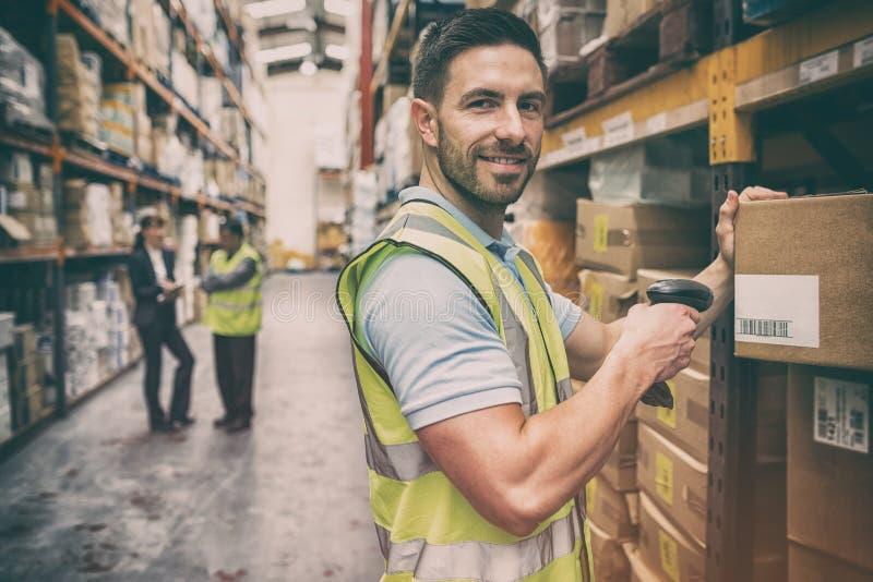 Magazynowy pracownika skanerowania pudełko podczas gdy ono uśmiecha się przy kamerą zdjęcie royalty free