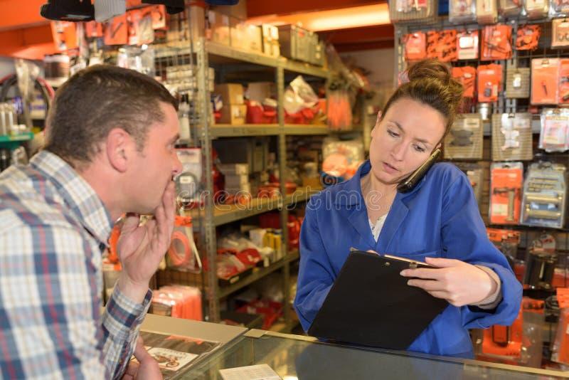 Magazynowy sklepu asystent na telefonie podczas gdy klient czeka zdjęcia royalty free