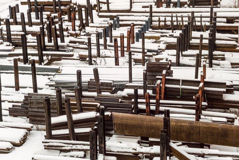 Magazzino all'aperto industriale dei tubi d'acciaio e dei prodotti metallici finiti Sito di stoccaggio ad orario invernale fotografia stock libera da diritti