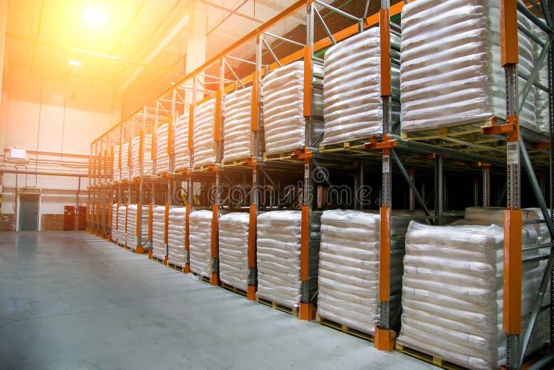 Magazzino del capannone con le file degli scaffali con i sacchi in polietilene bianchi con produzione finita della fabbrica fotografia stock