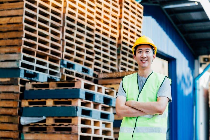 Magazzino e lavoratore dell'industria di logistica che sorride con le armi attraversate fotografie stock libere da diritti
