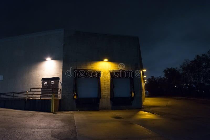 Magazzino scuro e spaventoso del magazzino della città alla notte fotografie stock