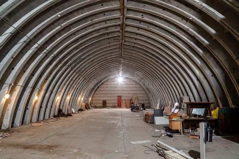 Magazzino vuoto abbandonato, vecchia costruzione metallica rustica con il tetto del metallo, interno di vecchia costruzione comme fotografia stock