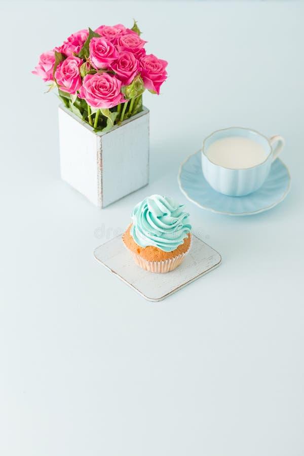 Magdalena con crema azul apacible y rosas rosadas en florero elegante lamentable retro en fondo en colores pastel azul fotografía de archivo libre de regalías