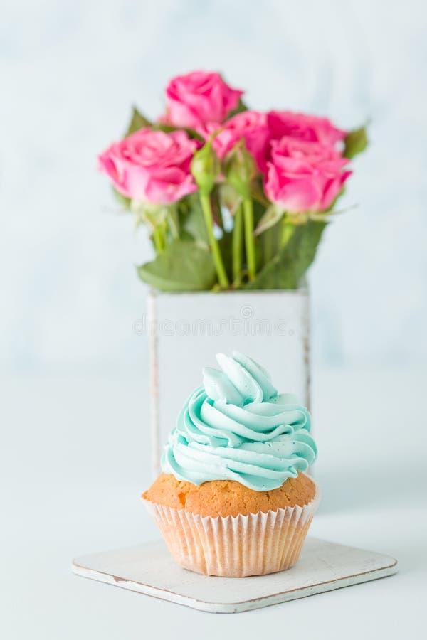 Magdalena con crema azul apacible y rosas rosadas en florero elegante lamentable retro en fondo en colores pastel azul imagen de archivo libre de regalías