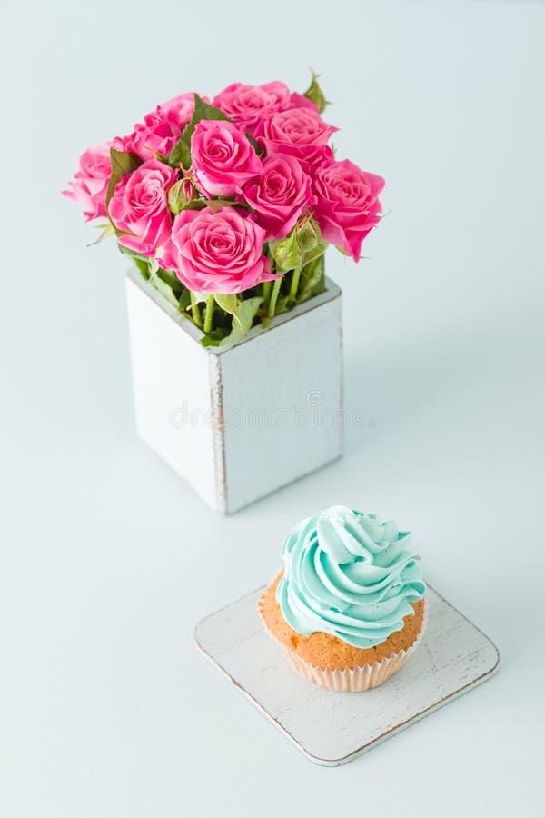 Magdalena con crema azul apacible y rosas rosadas en florero elegante lamentable retro en fondo en colores pastel azul foto de archivo libre de regalías