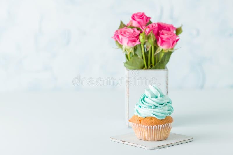 Magdalena con crema azul apacible y rosas rosadas en florero elegante lamentable retro en fondo en colores pastel azul imagenes de archivo
