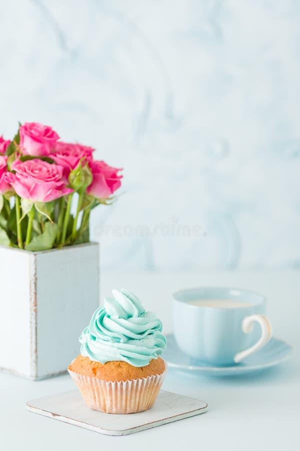 Magdalena con crema azul apacible y rosas rosadas en florero elegante lamentable retro en fondo en colores pastel azul foto de archivo