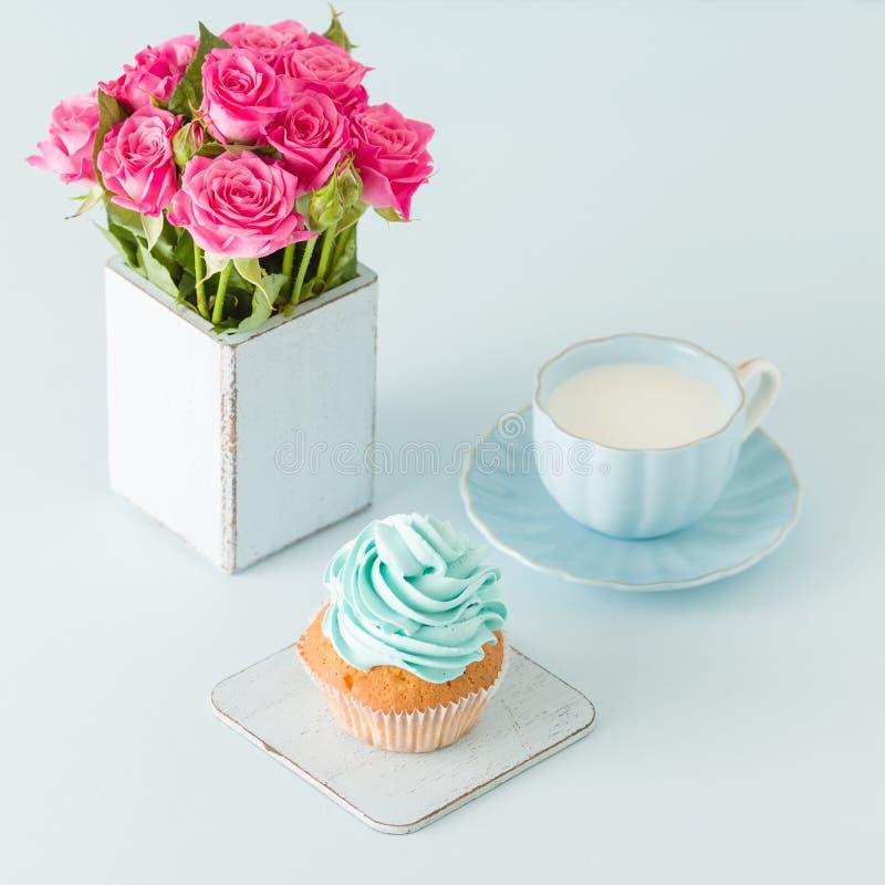 Magdalena con crema azul apacible y rosas rosadas en florero elegante lamentable retro en fondo en colores pastel azul imágenes de archivo libres de regalías