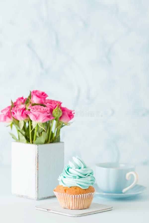Magdalena con crema azul apacible y rosas rosadas en florero elegante lamentable retro en fondo en colores pastel azul fotos de archivo