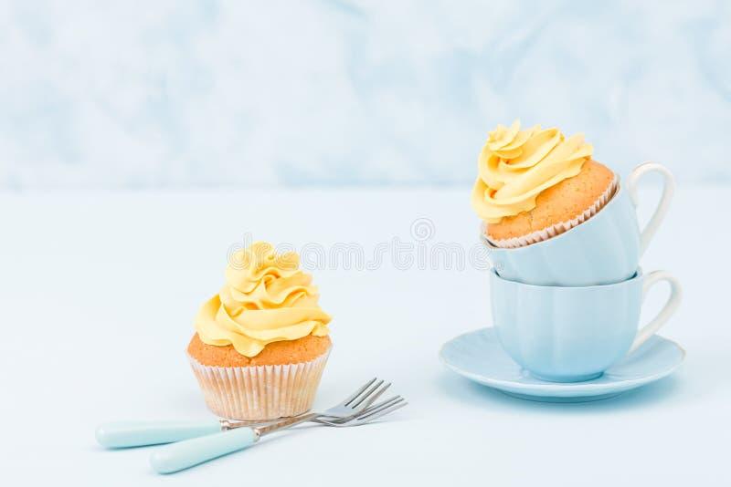 Magdalena con la decoración poner crema amarilla dulce en dos pequeñas tazas en fondo en colores pastel azul imagen de archivo libre de regalías