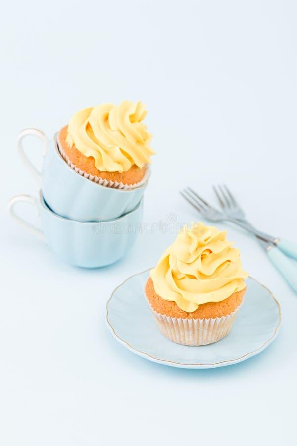 Magdalena con la decoración poner crema amarilla dulce en dos pequeñas tazas en fondo en colores pastel azul foto de archivo libre de regalías