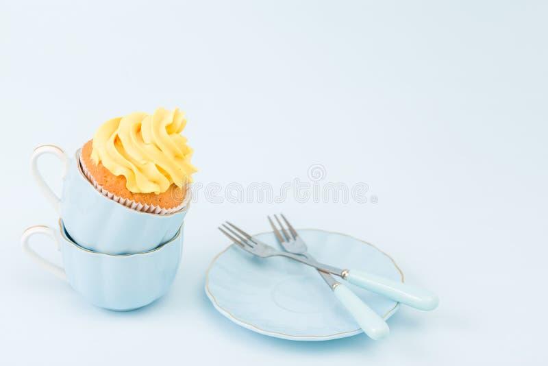 Magdalena con la decoración poner crema amarilla dulce en dos pequeñas tazas en fondo en colores pastel azul foto de archivo