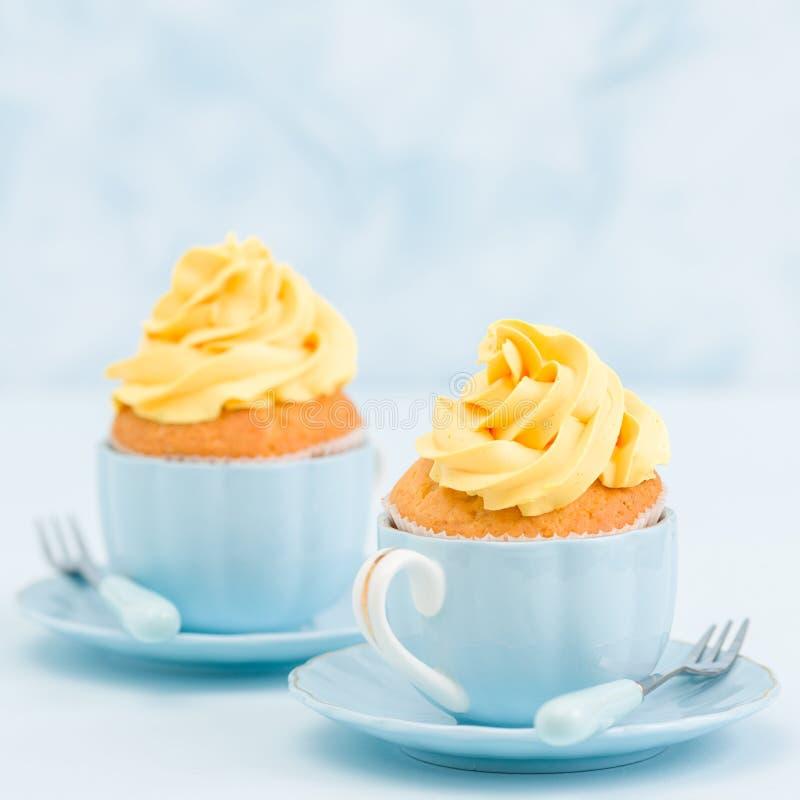 Magdalena con la decoración poner crema amarilla dulce en dos pequeñas tazas en fondo en colores pastel azul imagenes de archivo