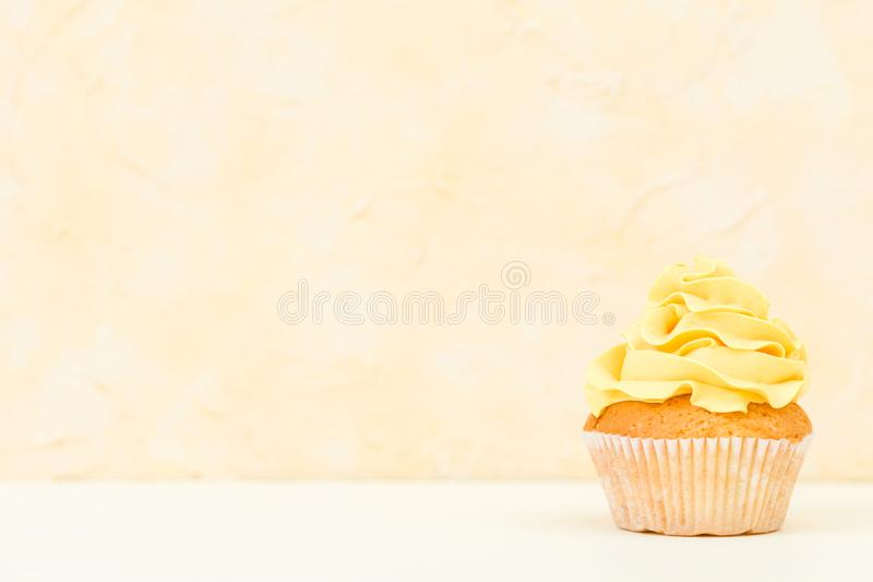 Magdalena con la decoración poner crema amarilla en el fondo amarillo - bandera horizontal en colores pastel Todavía del minimali imagen de archivo