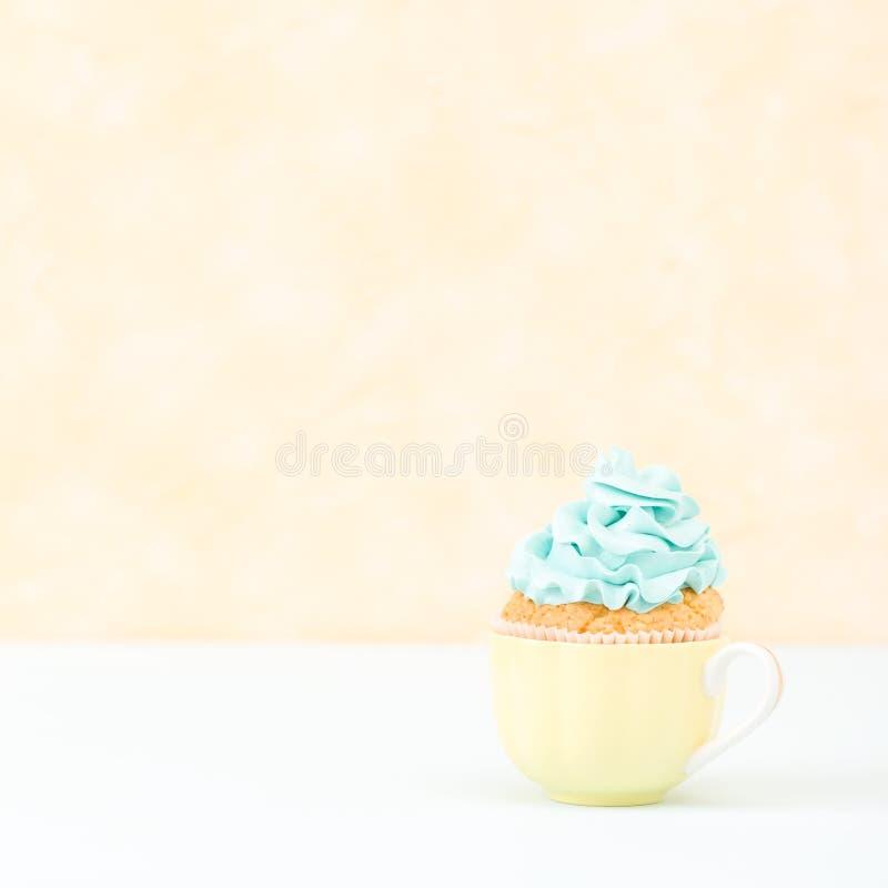 Magdalena con la decoración poner crema azul en la placa - bandera cuadrada en colores pastel amarilla Todavía del minimalismo co imagen de archivo libre de regalías