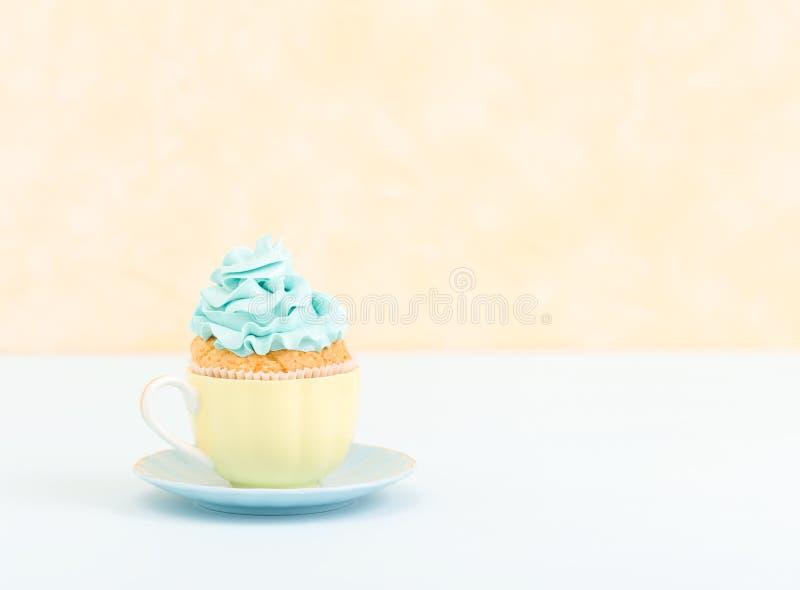 Magdalena con la decoración poner crema azul en la placa - bandera horizontal en colores pastel amarilla Todavía del minimalismo  imagen de archivo libre de regalías