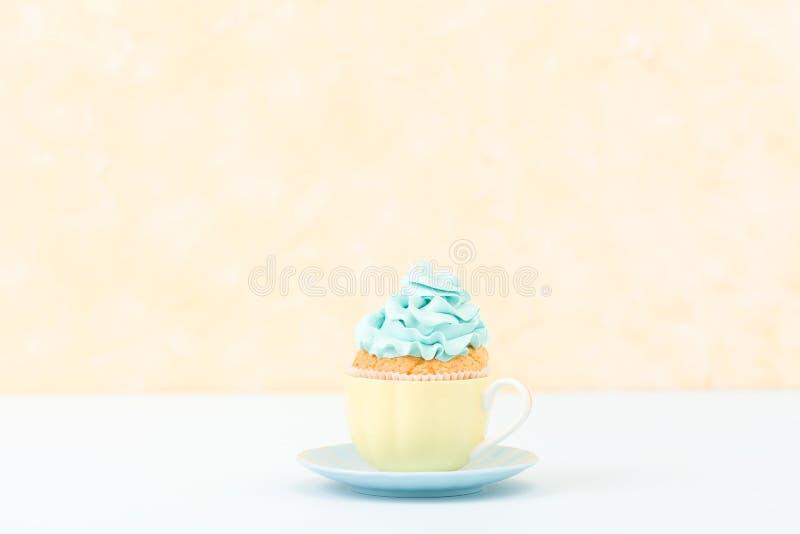 Magdalena con la decoración poner crema azul en la placa - bandera horizontal en colores pastel amarilla Todavía del minimalismo  imágenes de archivo libres de regalías