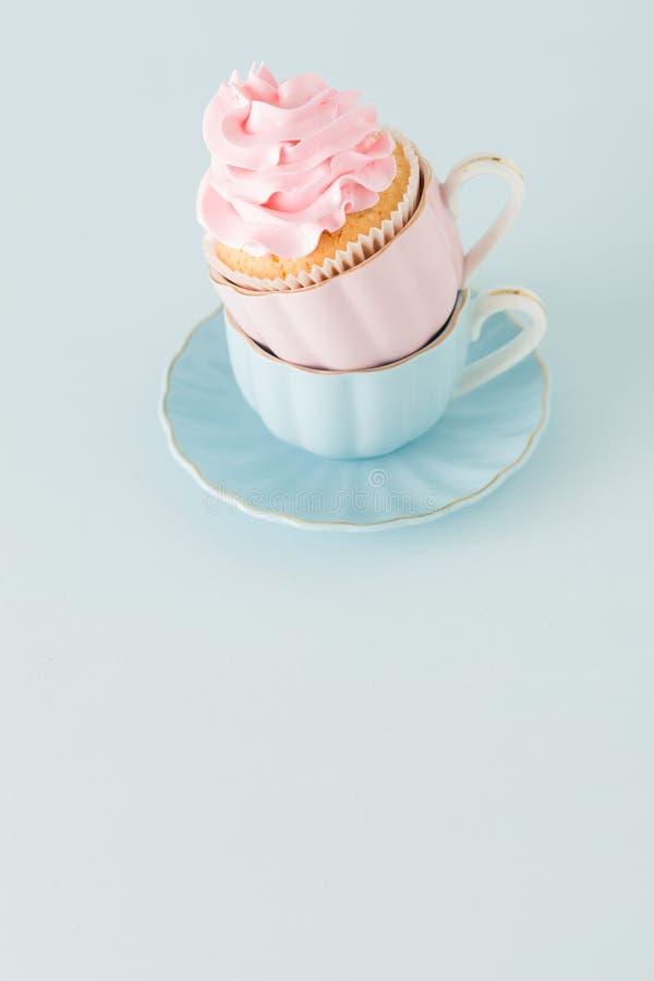 Magdalena con la decoración poner crema rosada apacible en dos tazas en fondo en colores pastel azul foto de archivo libre de regalías