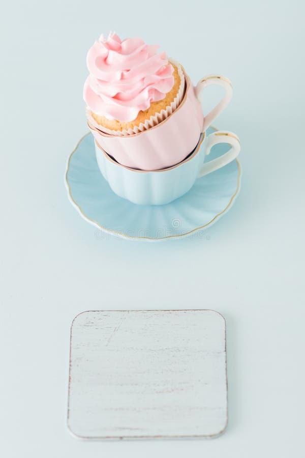 Magdalena con la decoración poner crema rosada apacible en dos tazas en fondo en colores pastel azul imagen de archivo libre de regalías