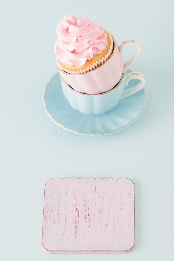 Magdalena con la decoración poner crema rosada apacible en dos tazas en fondo en colores pastel azul imagenes de archivo