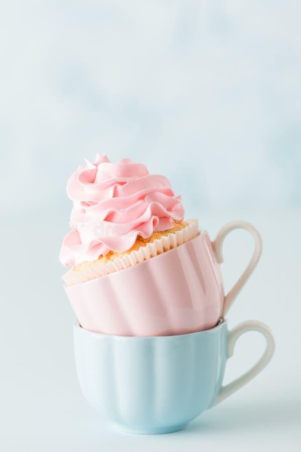 Magdalena con la decoración poner crema rosada apacible en dos tazas en fondo en colores pastel azul fotografía de archivo libre de regalías