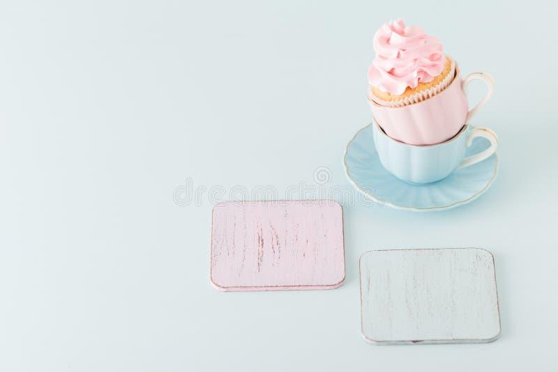 Magdalena con la decoración poner crema rosada apacible en dos tazas en fondo en colores pastel azul foto de archivo