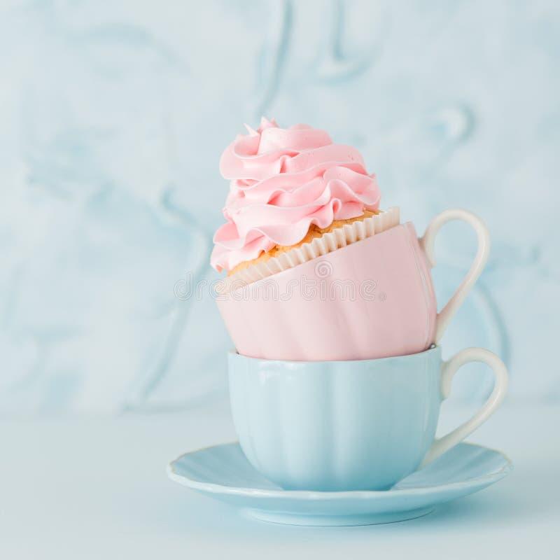 Magdalena con la decoración poner crema rosada apacible en dos tazas en fondo en colores pastel azul fotos de archivo libres de regalías
