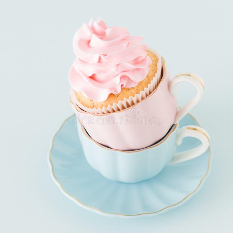 Magdalena con la decoración poner crema rosada apacible en dos tazas en fondo en colores pastel azul fotos de archivo