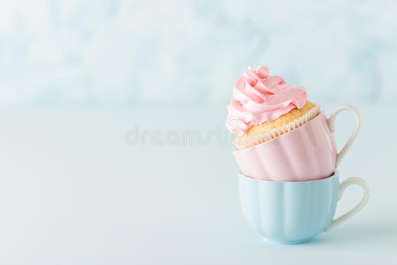 Magdalena con la decoración rosada del buttercream en dos tazas en fondo en colores pastel azul fotos de archivo libres de regalías