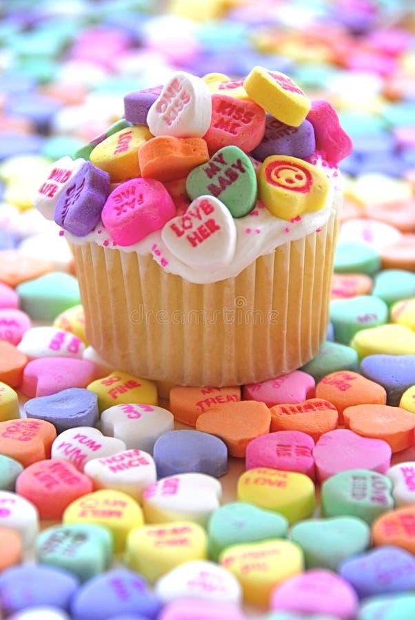 Magdalena de la tarjeta del día de San Valentín con los corazones del caramelo fotos de archivo