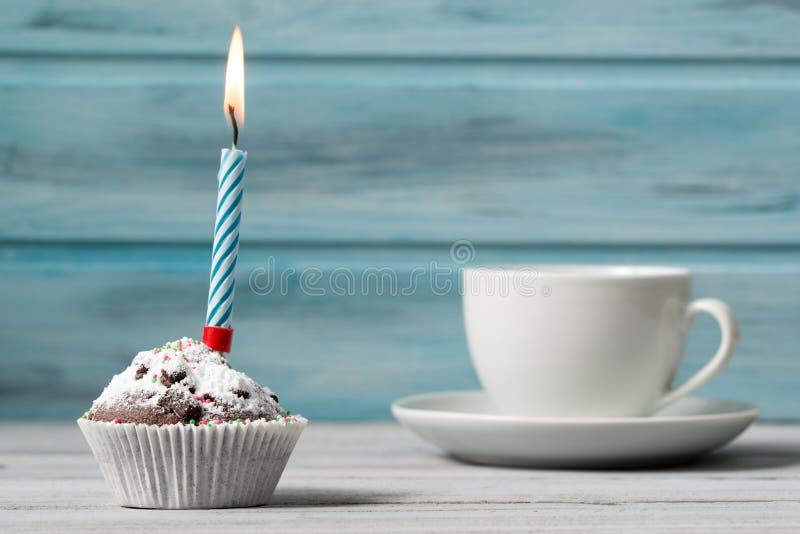 Magdalena del cumpleaños con la vela y taza de café, en fondo de madera imagen de archivo