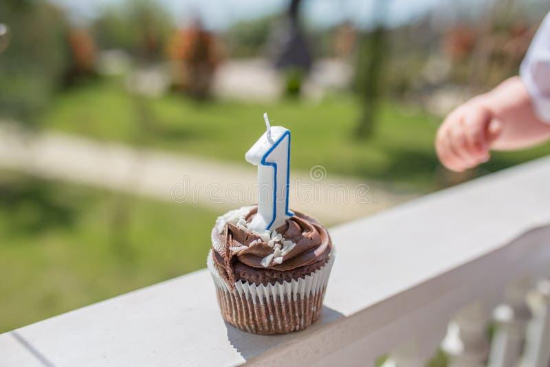 Magdalena del cumpleaños con número una vela con la poca mano del niño en fondo de la hierba fotografía de archivo libre de regalías