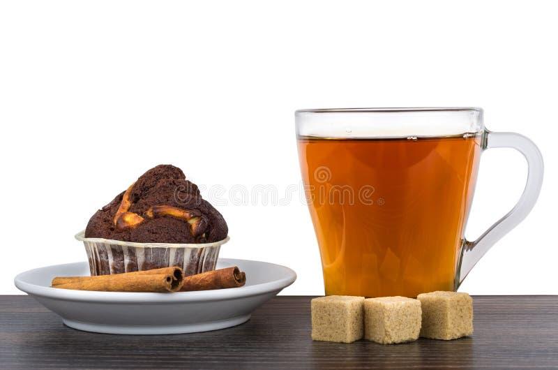 Magdalena, palillos de canela, azúcar y té aislados en blanco imágenes de archivo libres de regalías