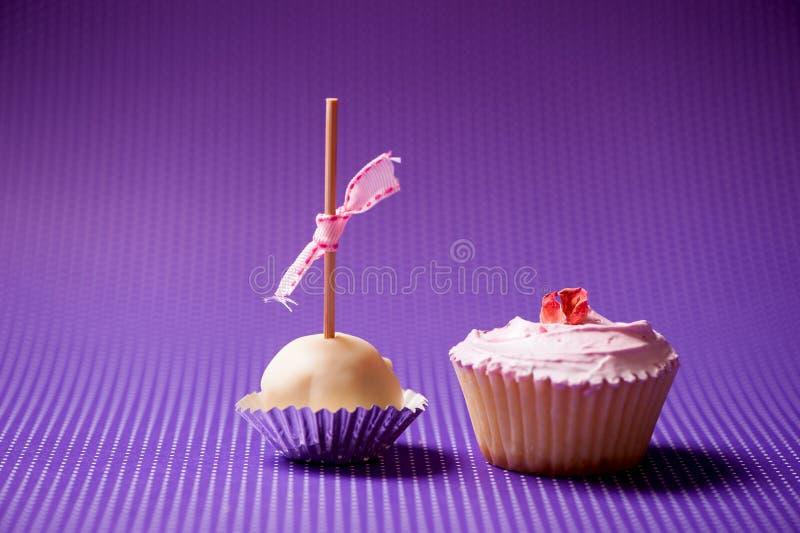 Magdalena y mollete en pasteles aislados en fondo púrpura fotos de archivo
