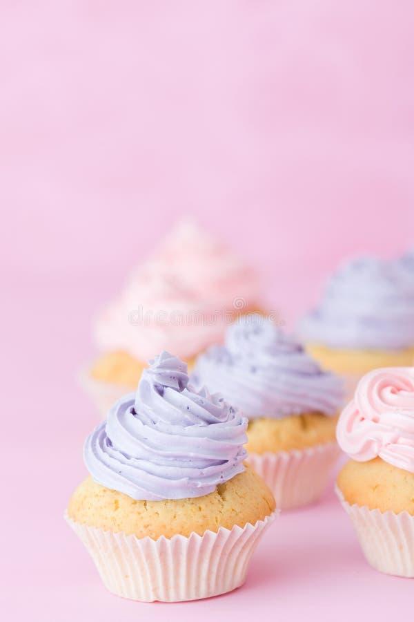 Magdalenas adornadas con el buttercream rosado y violeta que se coloca en fondo del rosa en colores pastel imagen de archivo libre de regalías