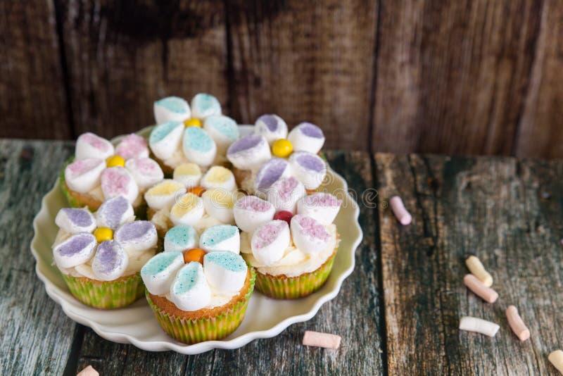 Magdalenas adornadas con las flores de la crema y de la melcocha de la mantequilla imagen de archivo