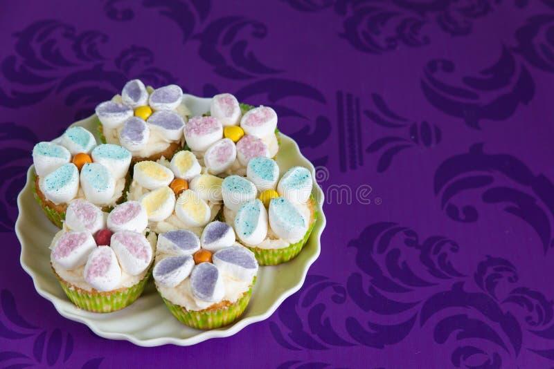 Magdalenas adornadas con las flores de la crema y de la melcocha de la mantequilla imagen de archivo libre de regalías
