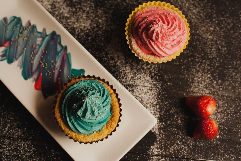 Magdalenas coloridas con la fresa imagen de archivo libre de regalías