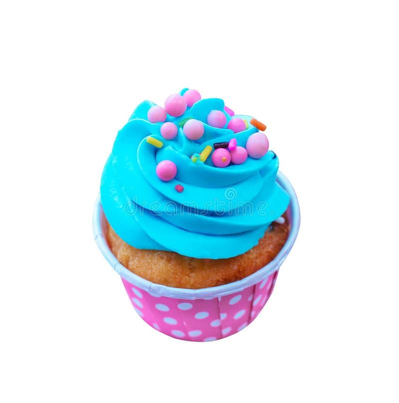 Magdalenas coloridas del día de fiesta con crema azotada azul y el desmoche multicolor en la taza de papel viva rosada aislada en fotografía de archivo