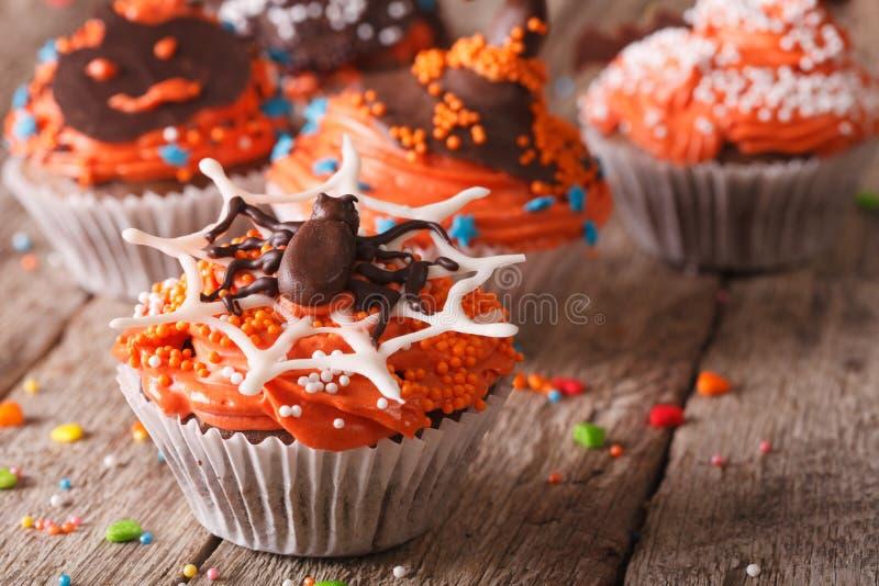 Magdalenas coloridas divertidas de Halloween en un primer de la tabla fotografía de archivo libre de regalías