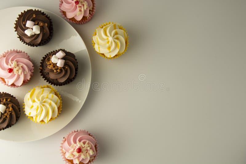 Magdalenas coloridas en un fondo blanco Magdalenas del rosa, amarillas y del chocolate Bocados sabrosos Partido dulce del postre  foto de archivo